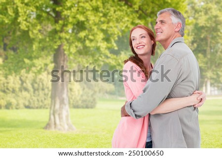 Casual couple hugging and smiling against trees and meadow - stock photo