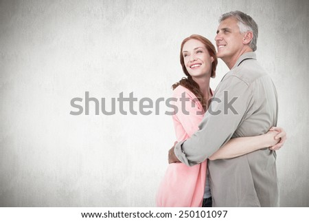 Casual couple hugging and smiling against white background