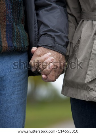 casual couple in their 60s holding hands together - stock photo