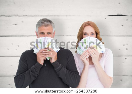 Casual couple showing their cash against white wood - stock photo