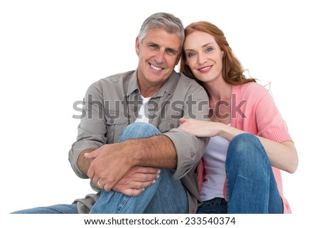 Casual couple sitting and smiling on white background - stock photo