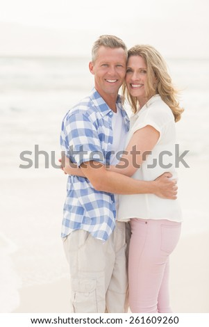Casual couple smiling at camera at the beach - stock photo