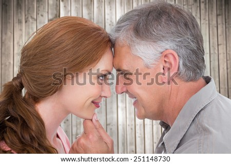 Casual couple smiling at each other against wooden planks background