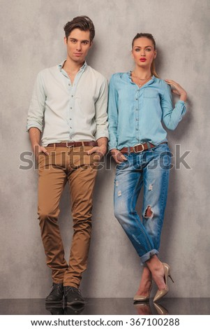 casual couple standing in studio leaning on the wall while posing with hands in pockets - stock photo