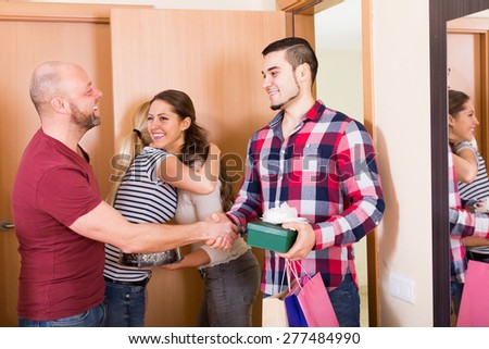 Casual couple welcomes friends at home - stock photo