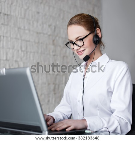 Casual customer support worker in office with headset and laptop - stock photo