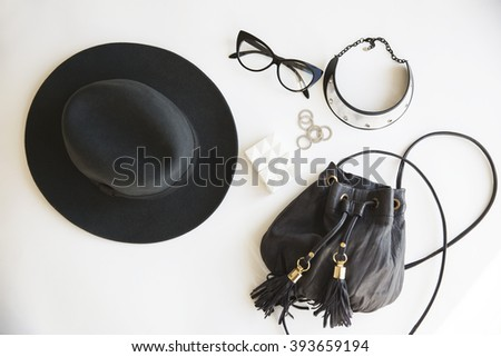 Casual day look. Outfit of young woman. Essentials for modern young lady. Different female accessories on white background: hat phone money glasses silver jewelry (rings) boho bag with tassels - stock photo