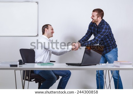 Casual dressed businessmen shaking hands - stock photo