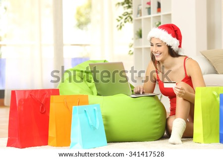 Casual girl buying online for christmas sitting on the floor with colorful shopping bags at home - stock photo