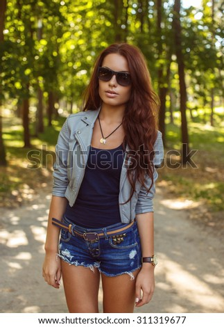 Casual girl in sunglasses in blue jeans shorts and grey jacket posing in green park.