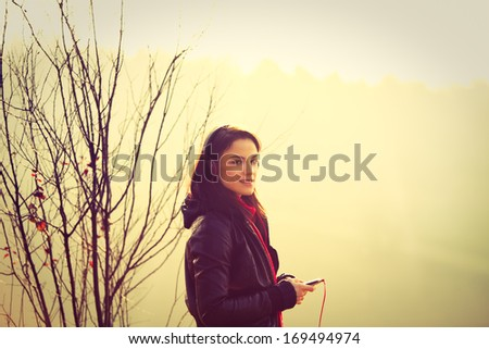 casual girl listen music outdoor winter day retro colors - stock photo