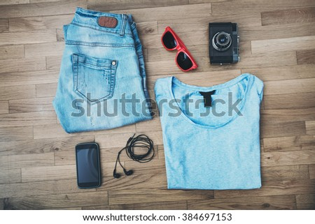 casual girl outfit background, blue jeans, t-shirt, smart phone, earphones, old camera and sunglasses