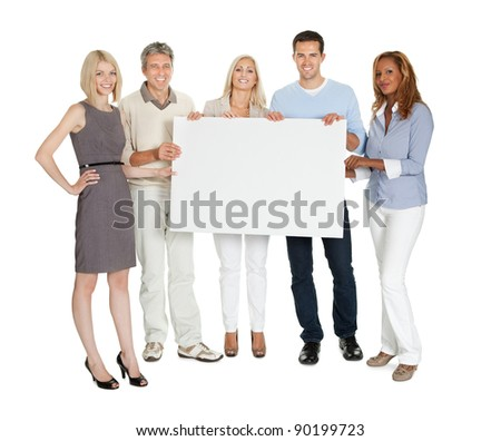 Casual group of people holding a blank billboard on white background - stock photo