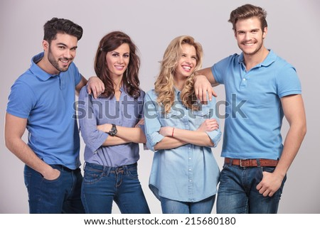 casual group of young people laughing together on grey studio background - stock photo