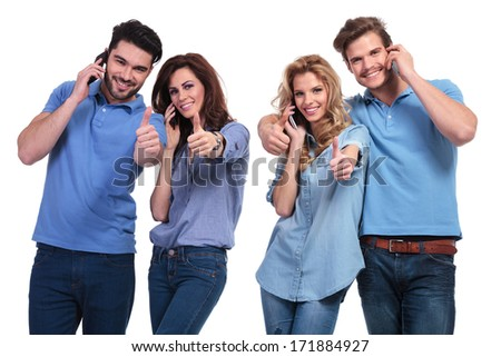 casual group of young people making the ok thumbs up sign while talking on the phone