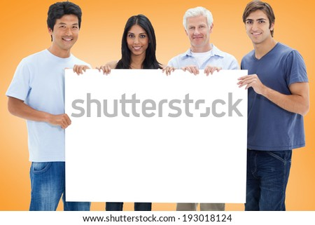 Casual group showing card against orange vignette - stock photo