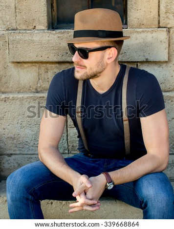 Casual handsome attractive man hipster guy with sunglasses and hat - stock photo