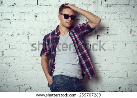 Casual handsome attractive man hipster guy with sunglasses with his hand in the hair - stock photo