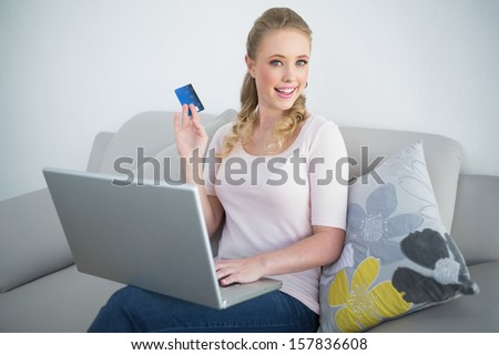 Casual happy blonde holding laptop and credit card in bright living room - stock photo