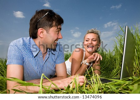 Casual happy couple are talking  and laughing on a laptop computer outdoors. Lay on the green grass. - stock photo