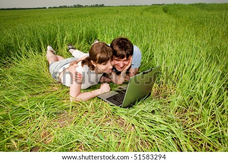 Casual happy couple on a laptop computer outdoors - stock photo