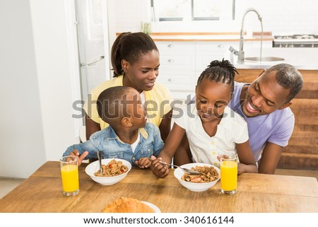 Casual happy family having breakfast in the kitchen - stock photo