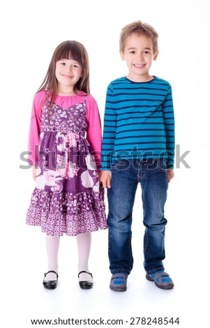 Casual happy little boy and girl standing and holding hands
