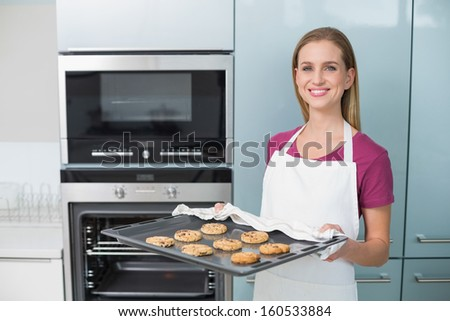Casual happy woman holding baking tray with cookies in bright kitchen - stock photo