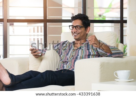 casual indian male using phone at livingroom - stock photo