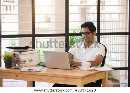 casual indian male working at office - stock photo
