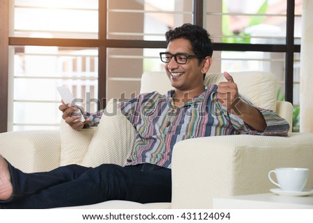 casual indian with smartphone male on sofa - stock photo