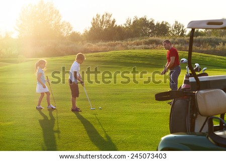 Casual kids at a golf field holding golf clubs studing with trainer. Sunset