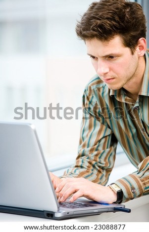 Casual looking businessman working on laptop computer in front of office window. - stock photo