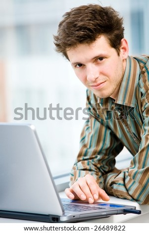 Casual looking happy businessman working on laptop computer in front of office window, smiling. - stock photo