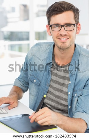 Casual male photo editor using graphics tablet in a bright office - stock photo