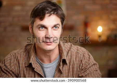 Casual man daydreaming, smiling. - stock photo