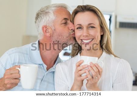 Casual man giving his smiling partner a kiss on the cheek at home in the kitchen - stock photo