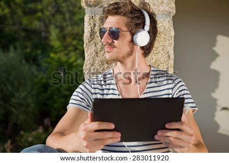 casual man holding a tablet with headphones, outdoor - stock photo