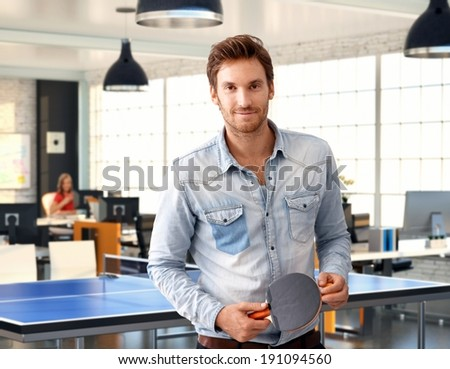 Casual man holding ping-pong racket at trendy office, smiling.