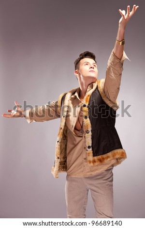 casual  man in a fur coat reaching out for the light on gray background - stock photo