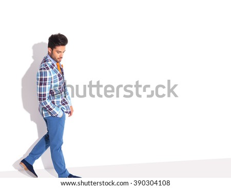 casual man in plaid jacket walking in studio background with hand in pocket while looking down, away from the camera - stock photo