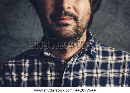 Casual man in plaid shirt smiling, thinking and contemplating, low key, selective focus portrait - stock photo