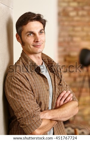 Casual man leaning against wall, smiling arms crossed, looking away. - stock photo