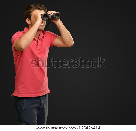 casual man looking into binocular isolated on black background