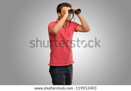 casual man looking into binocular isolated on grey background