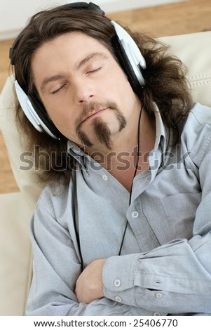 Casual man lying on couch at living room and listening music with headphones.