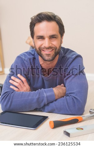 Casual man lying on floor using tablet pc for DIY instructions at home in the living room - stock photo