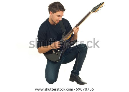 Casual man  playing electronic guitar and sanding on one knee isolated on white background