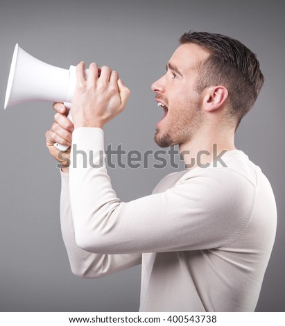 Casual man screaming with a megaphone on grey background - stock photo