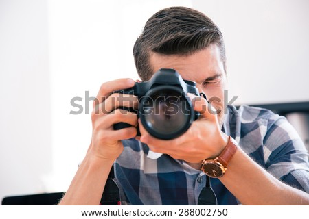Casual man shooting with photo camera - stock photo